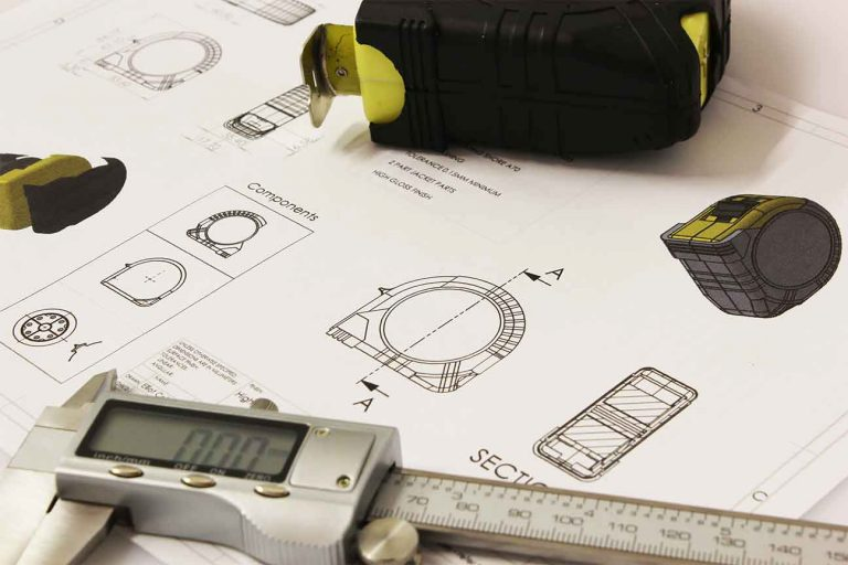 construction-drawing-on-table-next-to-calipers-and-measuring-tape